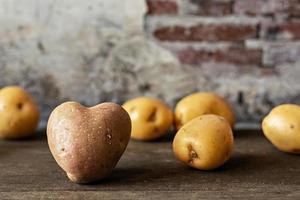 Herzförmige rote Kartoffel unter bestreuten weißen Kartoffeln auf Vintage-Hintergrund foto