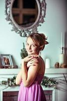 ein junges Mädchen in einem rosa Kleid auf dem Hintergrund von Weihnachtsdekorationen und einem Kamin im Zimmer foto