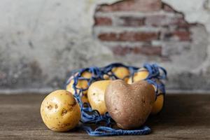 Herzförmige rote Kartoffeln mit weißen Kartoffeln in einem blauen Öko-Gitter auf einer hölzernen Hintergrundnahaufnahme foto