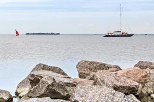Granitsteine im Wasser am Ufer des Finnischen Meerbusens. Segelboote schwimmen auf dem Wasser foto