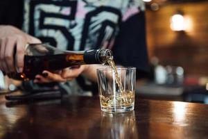 Whisky wird aus einer Flasche in ein Glas gegossen foto