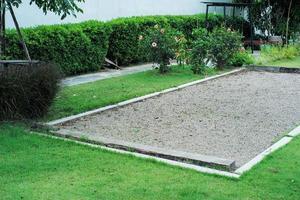 Landschaft der Rasenfläche mit Petanque-Platz im Garten des Hinterhofs foto