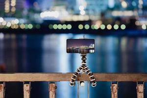 mit einem Smartphone auf einem faltbaren Stativ mit Langzeitbelichtung des Meeres bei Nacht foto