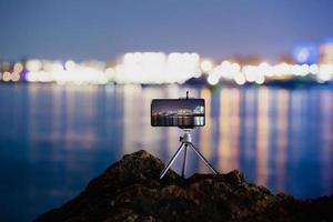 Verwenden eines Smartphones auf einem Stativ mit Langzeitbelichtung des Meeres bei Nacht foto