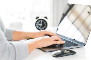 Geschäftsfrau, die auf Laptop zu Hause oder am Arbeitsplatz tippt. foto