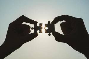 Silhouette der Nahaufnahme Frau und Mann Hand verbinden ein Stück Puzzle über Sonnenlicht-Effekt. Symbol für Assoziation und Verbindungskonzept. Geschäftsstrategie. foto