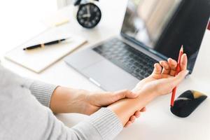 Nahaufnahmefrau, die ihre Handgelenkschmerzen von der Verwendung des Computers lange Zeit hält. Büro-Syndrom-Konzept. foto