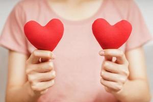 Frau mit rotem Herz, Liebe, Krankenversicherung, Spende, glücklicher Wohltätigkeits-Freiwilliger, Welttag der psychischen Gesundheit, Weltherztag, Valentinstag, foto