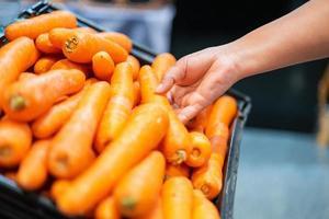 Frauenhand, die Karotte im Supermarkt aufhebt. Frau kauft in einem Supermarkt ein und kauft frisches Bio-Gemüse. Konzept für gesunde Ernährung. foto