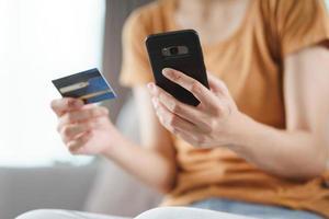 junge Frau, die Kreditkarte hält und Smartphone für Online-Shopping, Internet-Banking, E-Commerce, Geldausgeben, Arbeiten von zu Hause aus verwendet foto