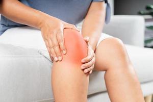 Nahaufnahme einer molligen Frau, die auf dem Sofa sitzt und Knieschmerzen verspürt und ihr Knie massiert. Gesundheits- und medizinisches Konzept. foto