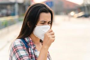asiatische Frau, die eine n95-Maske trägt, um die Verschmutzung PM2.5 und das Virus zu schützen. Covid-19 Coronavirus und Luftverschmutzung pm2.5 Konzept. foto