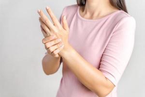 Closeup junge Frau hält ihr Handgelenk auf weißem Hintergrund. Handverletzung, Schmerzempfinden. Gesundheitsversorgung und medizinisches Konzept. foto