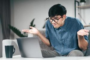 verwirrter ahnungsloser Mann, der Laptop-Computer für Videokonferenzanrufe verwendet, achselzuckend, keine Ahnung, welche Geste ich nicht kenne, wen interessiert das Konzept? foto