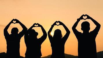 Gruppe von Menschen mit erhobenen Armen und Hand zur Herzform mit Blick auf den Sonnenaufgang auf dem Berghintergrund. Glück, Erfolg, Freundschaft und Gemeinschaftskonzepte. foto
