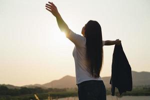 glückliche Geschäftsfrau, die Arme ausbreitet und die Bergsilhouette beobachtet. Geschäftserfolgskonzept, Freiheitsgefühle foto