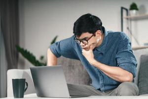 Nachdenklicher, ernster asiatischer Mann mit Brille, der den Laptop-Bildschirm betrachtet und nach einer Lösung zur Lösung des Problems denkt. foto