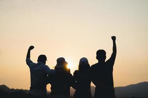 Gruppe von Menschen mit erhobenen Armen, die den Sonnenaufgang auf dem Berghintergrund betrachten. Glück, Erfolg, Freundschaft und Gemeinschaftskonzepte. foto