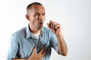 Mann, der über seine Hand niest oder hustet, um zu verhindern, dass sich das Virus Covid-19 oder das Corona-Virus auf weißem Hintergrund ausbreitet. foto