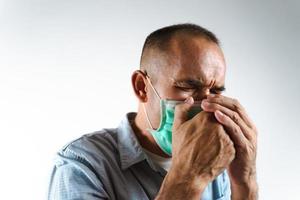 Mann mit Gesichtsmaske, der über seine Hand niest oder hustet, um zu verhindern, dass sich das Virus Covid-19 oder das Corona-Virus auf weißem Hintergrund ausbreitet. foto