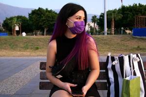 eine lilahaarige Frau mit Einkaufstüten. Shopping junge Frau ruht im Park sitzen. Sie trägt wegen Covid 19 eine lila Maske auf seinem Gesicht. foto