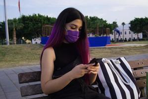eine lilahaarige Frau mit Einkaufstüten. Handy in ihrer Hand ruht im Park. Sie trägt wegen Covid 19 eine lila Maske auf seinem Gesicht. foto