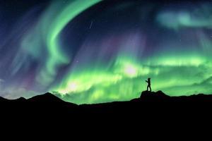 Mann wandert auf einem Berg mit Nordlichtexplosion hiking foto
