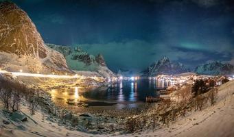 Panorama von Aurora Borealis über skandinavisches Dorf im Winter foto