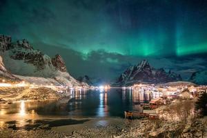 Aurora Borealis über skandinavisches Dorflicht, das im Winter scheint foto