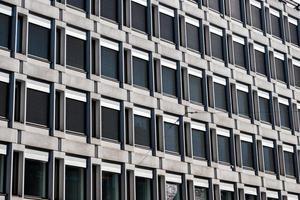 Reihe schwarzes Fenster auf Betongebäude foto
