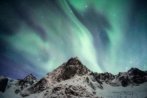 verschneite Montierung mit Aurora Borealis tanzen mit Sternschnuppe foto