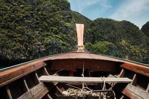 Der Blick von einem traditionellen thailändischen hölzernen Bugboot beim Schwimmen in der Bucht bietet einem Touristen eine wunderschöne Landschaft der natürlichen Meereslandschaft, sowohl der Berge als auch des Meeres auf der Insel Phi Phi. foto