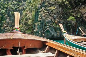 An den türkisfarbenen Stränden von Koh Phi Phi in Thailand liegen langschwänzige Boote vor Anker, um Touristen zu bedienen. Mit Blick auf den Bug in Richtung Rocky Mountain ist diese Küste ein Sommerziel für Reisen und Reisen. foto