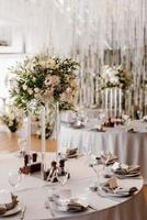das Präsidium des Brautpaares im Festsaal des Restaurants ist mit Kerzen und Grünpflanzen geschmückt foto