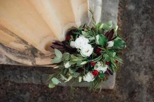 Hochzeitsstrauß aus roten Blumen und Grün foto