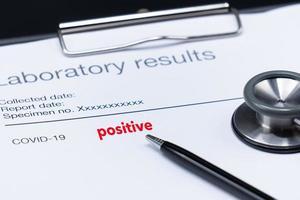 Laborergebnisse eines Patienten, der positiv auf Covid 19 oder Corona-Virus mit einem rosa Stethoskop auf schwarzem Hintergrund ist foto