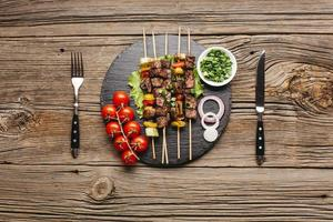 leckerer Fleischspieß schwarzer Schiefer mit Gabel Buttermesser Holztisch foto