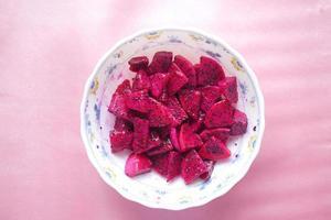 Stück Drachenfrucht auf in einer Schüssel auf rosa Hintergrund foto
