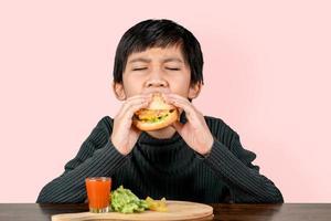 süßer asiatischer Junge, der mit Glück einen leckeren Hamburger isst foto