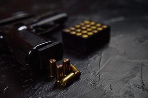 Pistole mit Patronen auf schwarzem Betontisch. foto