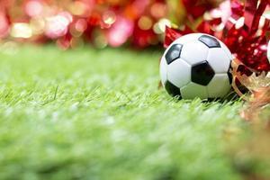 Fußball mit Weihnachtsdekoration auf grünem Gras foto
