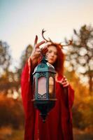 Frau im langen roten Kleid mit Hirschhörnern foto