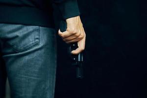 Mann in dunkler Kleidung hält Pistole. foto