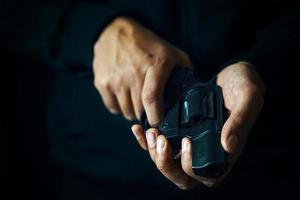 Kerl hält Revolver in den Händen. foto