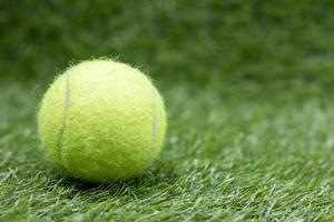 Tennisball liegt auf grünem Gras foto