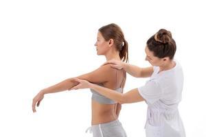 Patientin bei der Physiotherapie, die körperliche Übungen mit Chiropraktiker macht foto
