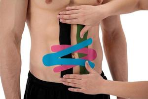 ein Therapeut klebt helle Kinesio-Tapes an Bauch oder Bauch eines Mannes foto