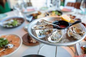 Platte mit frischen organischen rohen Austern auf Eis im Restaurant. Austern auf dem Servertisch foto