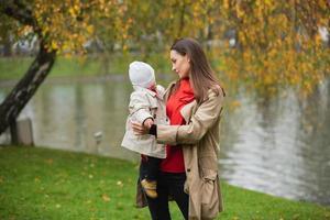 Mama und ihr Baby gehen mit ihrer kleinen Tochter im Arm durch den Herbstpark. ein See hinter ihnen foto