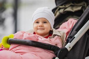 Babysitting im Kinderwagen, offene Augen, in Hut und Jacke, Winter- oder Herbstzeit. Porträt. foto